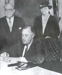 President Roosevelt signing the National Labor Relations Act into law on July 5, 1935, with Labor Secretary Frances Perkins looking on.